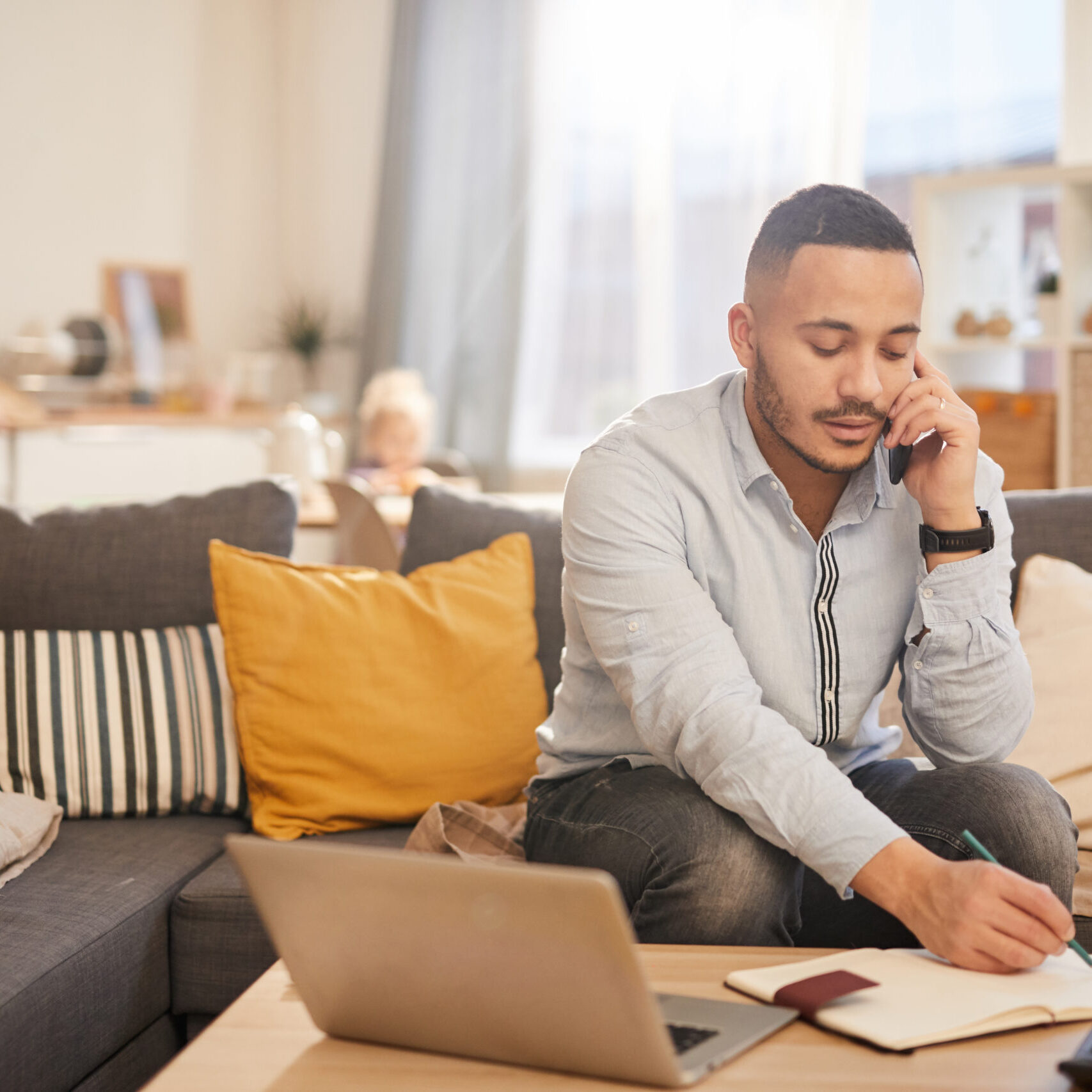 Portrait of modern mixed race man speaking by phone while working from home in cozy interior, copy space